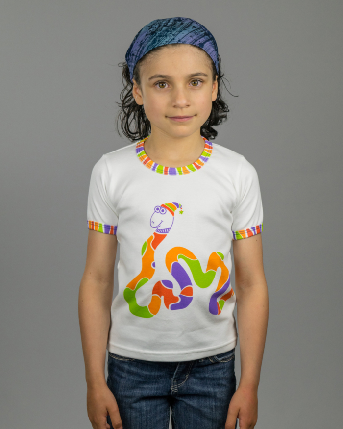 Image showing front side of Rainbow Snake kids t-shirt on girl model. Colorful winding snake from front to back of t-shirt with neck and arm bindings to match.